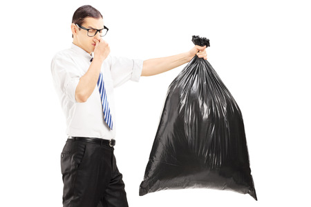 unpleasant: Male closing his nose and carrying a stinky garbage bag isolated on white background