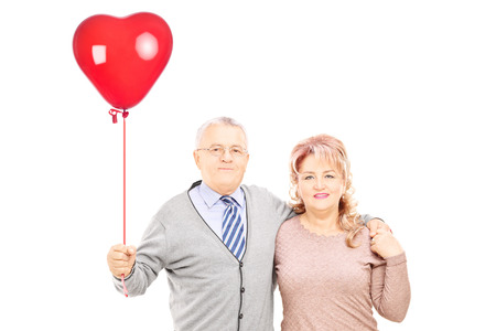 Middle aged couple in hug holding a red heart balloon isolated on white background photo