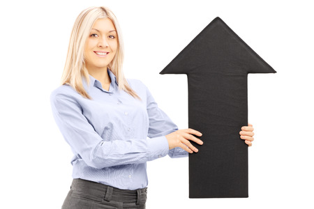 directive: Blond smiling woman holding a big black arrow pointing up isolated on white background