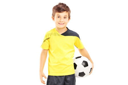 plimsoll: Kid in sportswear holding a soccer ball isolated on white background Stock Photo