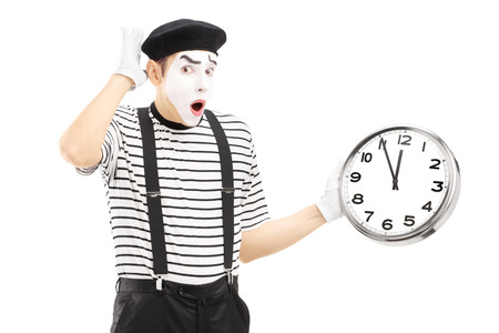 late 20s: Male mime holding a clock and gesturing late, isolated on white background