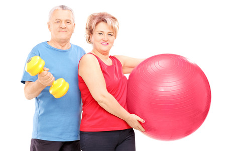 Mature man and woman posing with exercising equipment isolated on white background photo