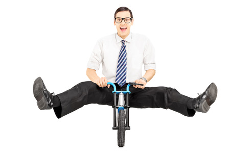 Excited young businessman with tie riding a small bicycle isolated on white background photo