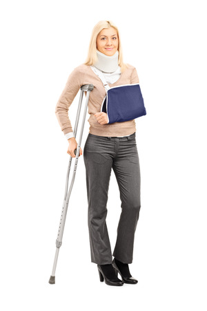 crutch: Full length portrait of a happy blond female with broken arm holding a crutch posing isolated on white background Stock Photo