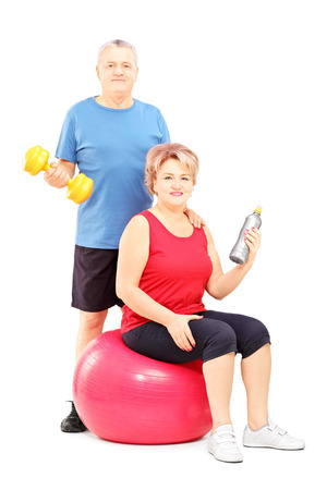 Mature man and woman posing with exercising equipment isolated against white background photo