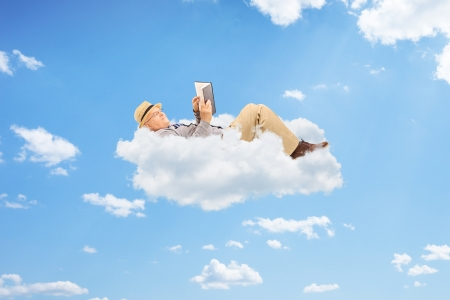 Senior male reading a book on clouds photo