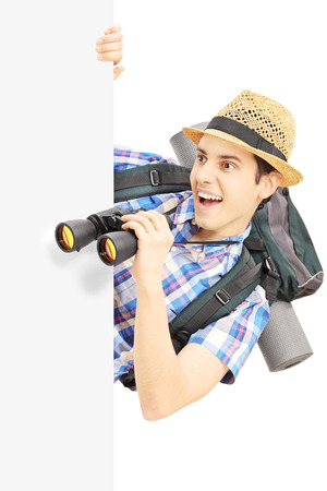Smiling male tourist looking through binocular behind a panel isolated on white background photo