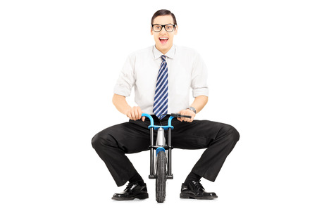 Smiling young businessman with tie on a small bicycle isolated on white background photo