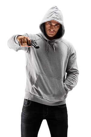 holding gun to head: Young male with hood over his head holding a gun, symbolizing crime isolated against white background Stock Photo