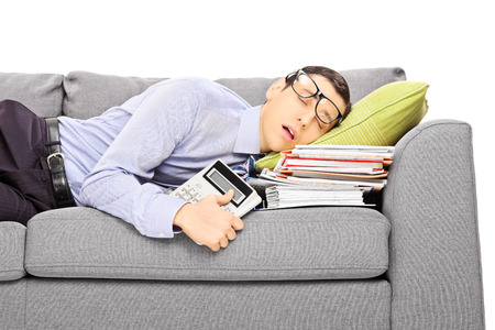 hardworking: Exhausted young businessman sleeping on a couch with many document, isolated on white background