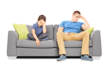dissappointed: Dissappointed brothers sitting on a sofa isolated on white background
