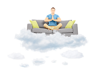 Guy meditating on a sofa and floating on a cloud isolated against white background photo