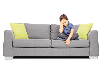 Sad boy sitting on a couch, isolated on white background Stock Photo - 24829258
