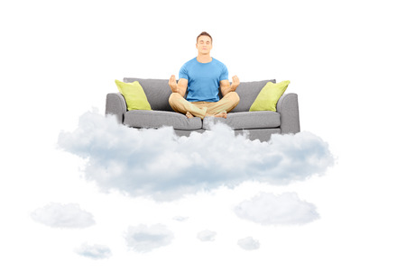 Young male meditating on a sofa and floating on a cloud isolated on white background photo