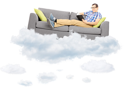 Young male on a couch reading a book and floating on a cloud isolated on white background photo