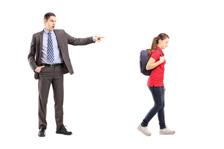 Full length portrait of angry father yelling at his daughter, isolated on white background  photo