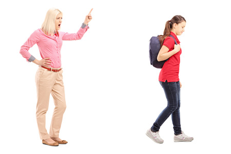Full length portrait of angry mother yelling at her daughter, isolated on white background photo