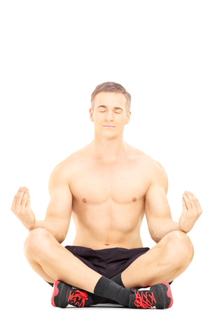 Handsome shirtless man meditating seated on a floor isolated on white background photo