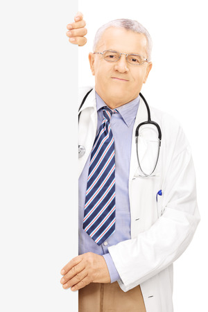 Middle aged doctor standing next to a blank panel, isolated on white background photo