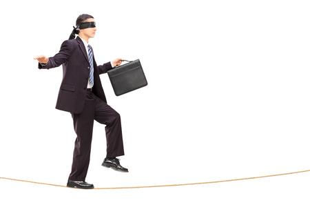 ojos vendados: Retrato de cuerpo completo del hombre de negocios con los ojos vendados caminando sobre la cuerda, aislado en fondo blanco Foto de archivo