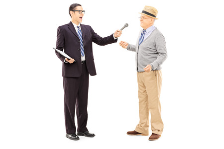 interviewing: Full length portrait of young man conducting survey on middle aged man with microphone in his hand, isolated on white background