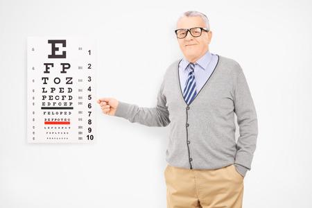 examen de la vista: Hombre de mediana edad con gafas apuntando hacia de la vista,