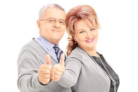 Smiling mature couple giving thumbs up and looking at camera, isolated on white background photo