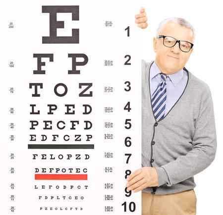 examen de la vista: Senior hombre de pie detrás de prueba de la vista, aislados en fondo blanco, disparó con una lente de inclinación y desplazamiento