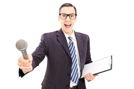 Excited young male interviewer in suit holding microphone, isolated on white background photo