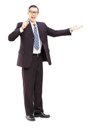 Ritratto integrale di un microfono che tiene annunciatore maschio, isolato su sfondo bianco