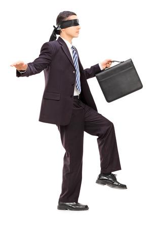 ojos vendados: Retrato de cuerpo completo del hombre de negocios con los ojos vendados con maletín caminando, aisladas sobre fondo blanco