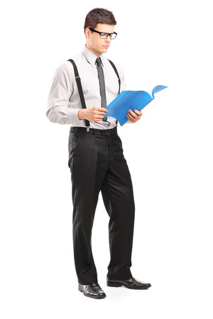 fascicule: Full length portrait of young man reading papers, isolated on white background Stock Photo
