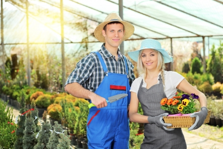 horticulturist: Male and female gardeners with basket full of flowers and small shovel posing in hothouse