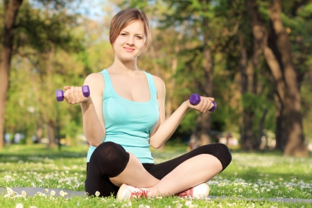 Female athlete exercising with dumbbells in a park photo