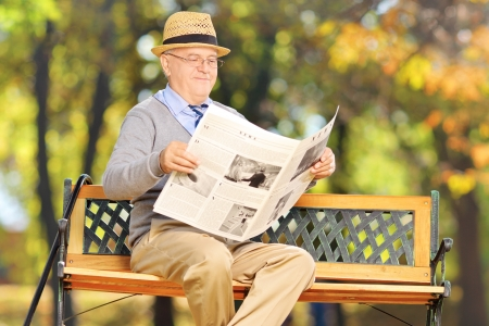 Senior gentleman seated on a bench reading a newspaper in a park photo