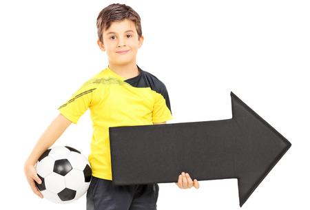 plimsoll: Smiling boy in sportswear holding a soccer ball and black arrow pointing right isolated on white background