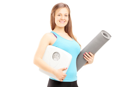 Smiling female athlete holding a weight scale and mat isolated on white background photo