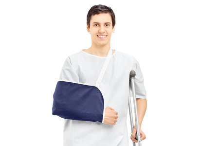 Smiling male patient in hospital gown with broken arm holding a crutch isolated on white background