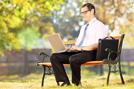 Young businessperson sitting on a bench and working on a laptop in a park photo