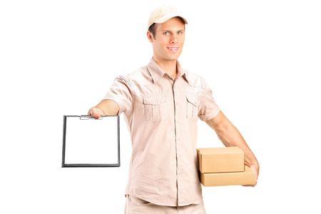 Delivery boy holding a packet and giving a clipboard for signature isolated on white background Stock Photo - 24935059