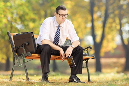sitting on a bench: Disappointed businessman sitting on a wooden bench with bottle in his hand, in park