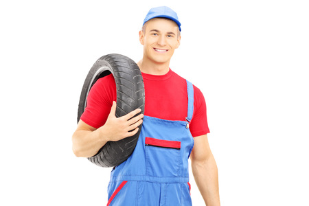 Male mechanic holding a vehicle tires and looking at camera isolated on white background Stock Photo - 24935067