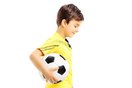 plimsoll: Sad kid in sportswear posing with a soccer ball isolated on white background