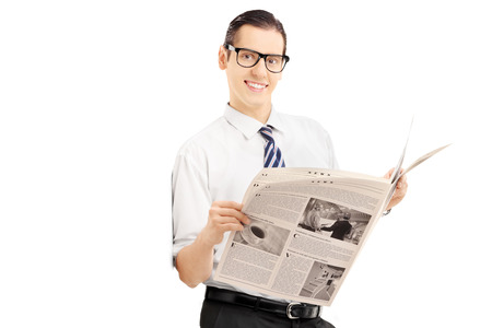 Smiling businessman leaning against wall and holding a newspaper isolated on white background photo