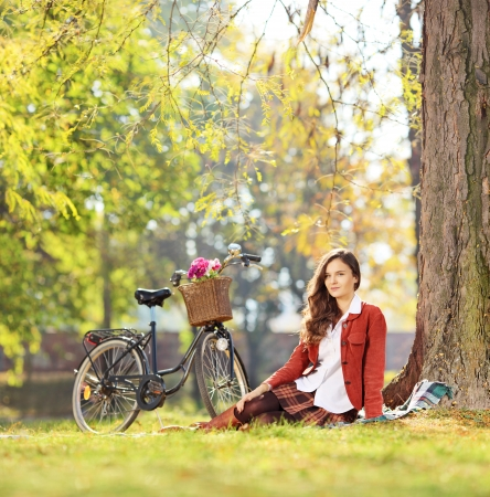 bycicle: Beautiful young female with bicycle sitting in park and looking at camera, shot with a tilt and shift lens