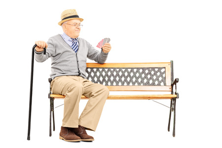 old man sitting: Senile old man with cane, sitting on bench imagining playing cards with someone else, isolated on white background Stock Photo