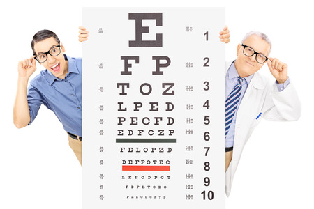 oculista: Hombre joven y una óptica con gafas de pie detrás de prueba de la vista, aislados en fondo blanco Foto de archivo