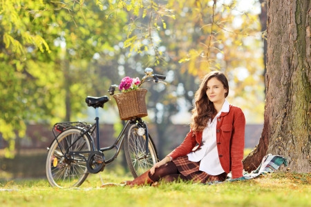 bycicle: Beautiful female with bicycle sitting in a park and looking at camera