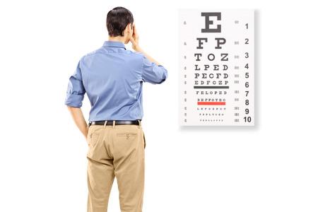 examen de la vista: Retrato de una prueba de la vista hombre que toma, aislado en fondo blanco Foto de archivo