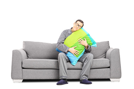 Sleepy guy in pajamas, sitting on sofa embracing a pillow, isolated on white background